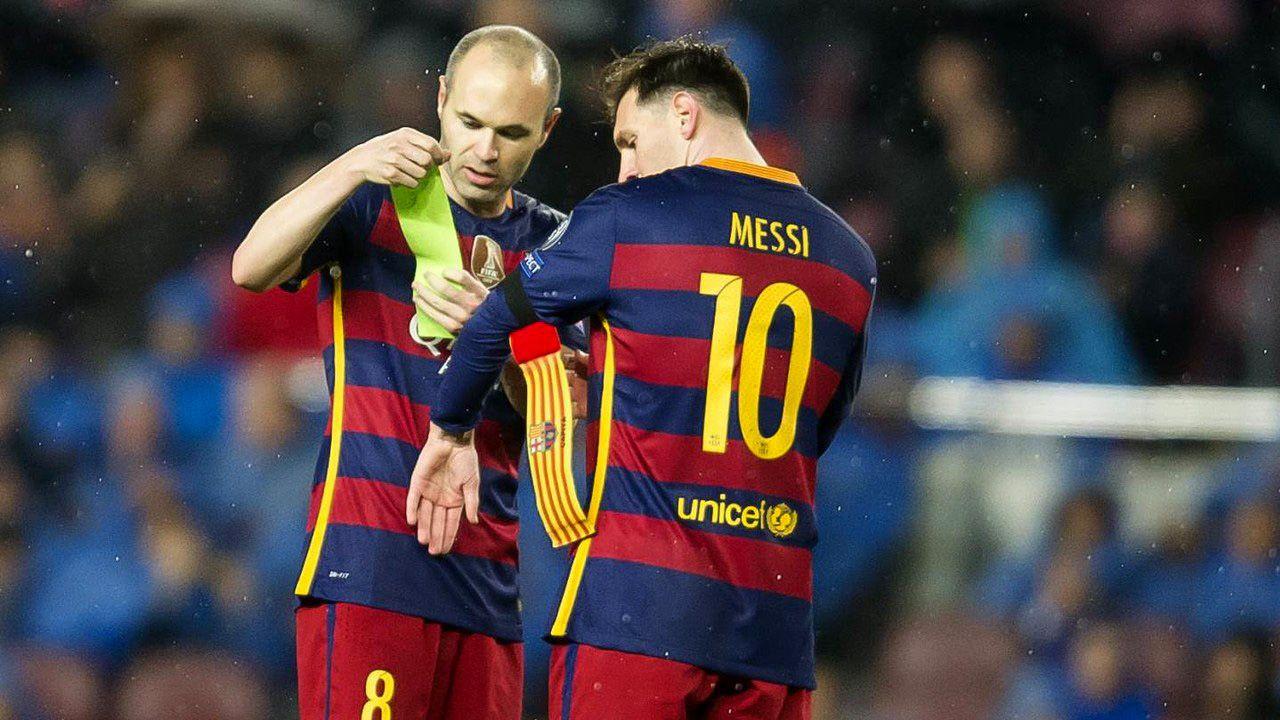 Andrés Iniesta cediéndole la cinta de capitán a Lionel Messi<br>