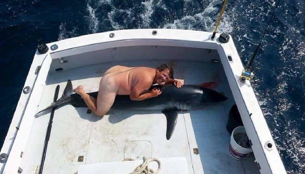 Cazó a un tiburón y posó desnudo con el animal ensangrentado