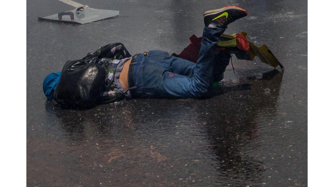 Un joven caído en el asfalto durante las protestas en Venezuela