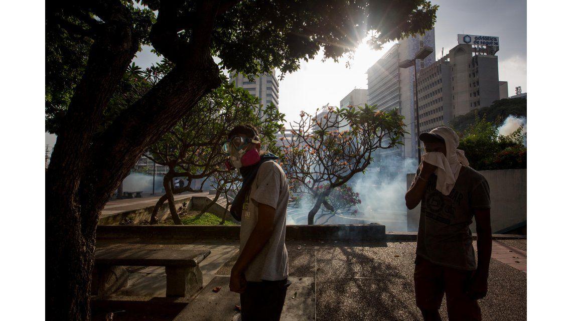 Jóvenes se protegen de los gases lacrimógenos