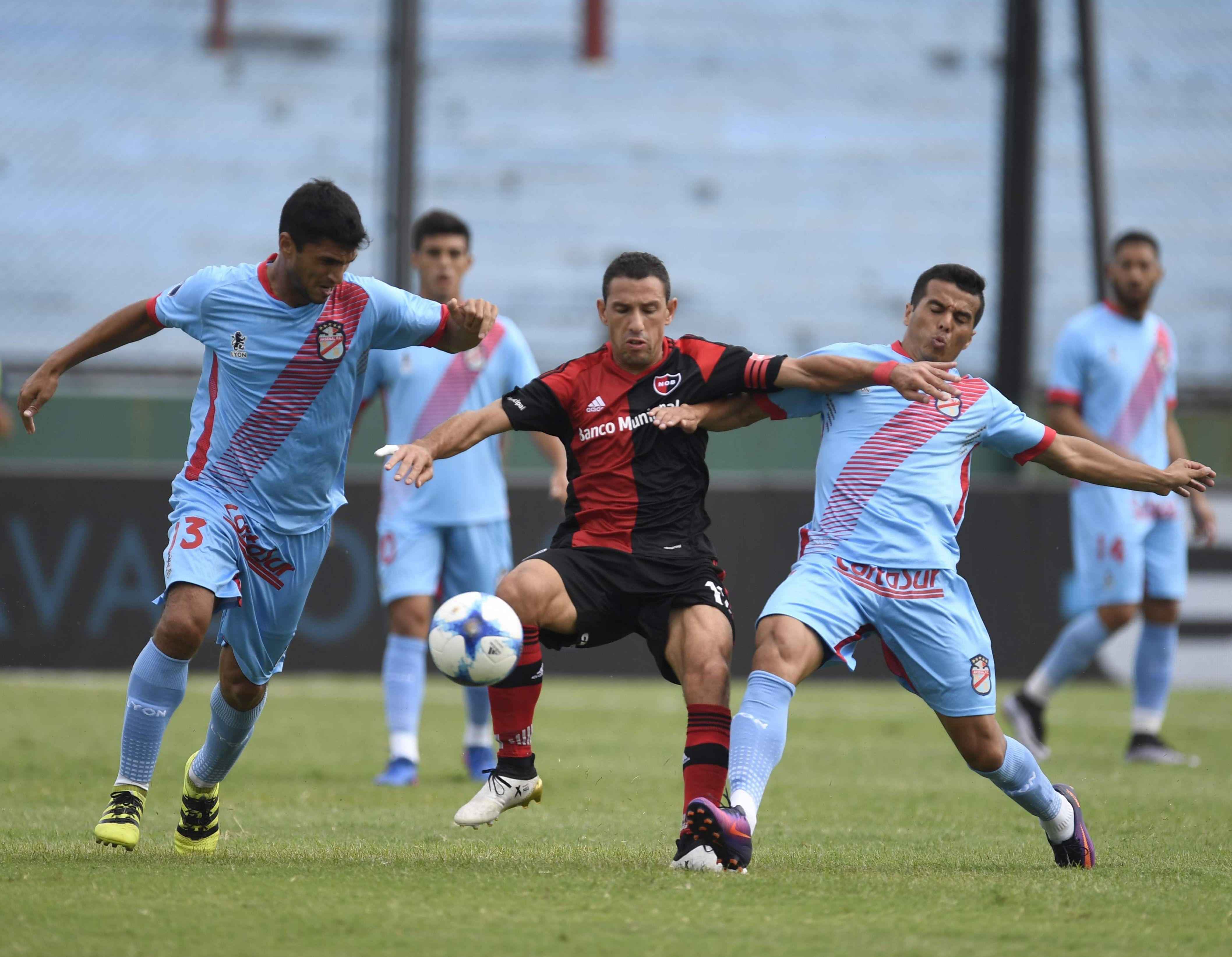 Maxi Rodríguez peleando por la pelota contra dos rivales