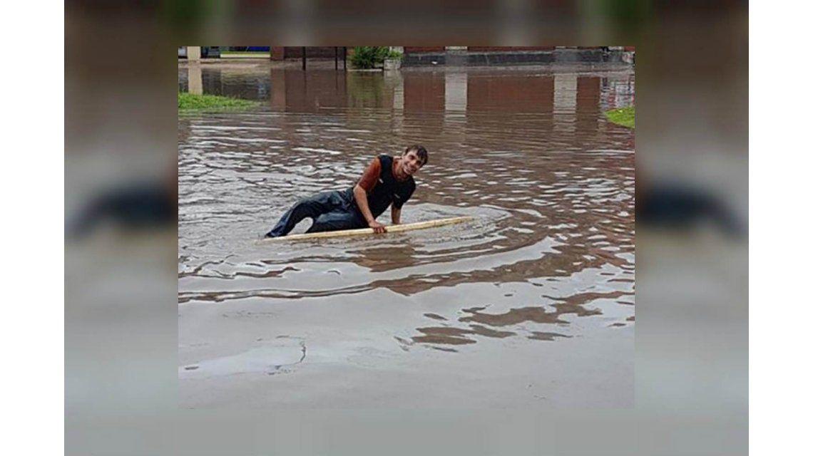 Salió a surfear en la calle inundada en medio del temporal