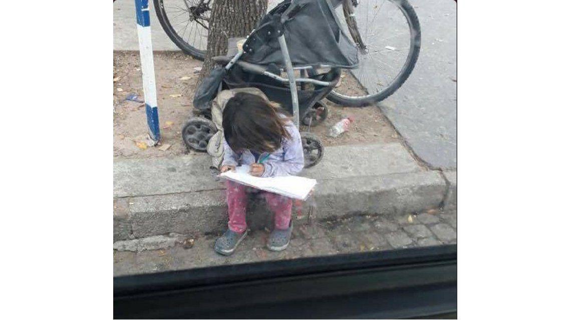 La nena haciendo los deberes mientras pide limosna