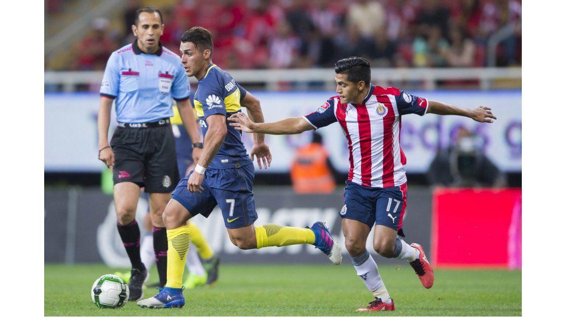 Cristian Pavón se lleva la pelota pese al intento de su rival