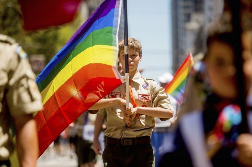Un boy scout porta la bandera del orgullo gay