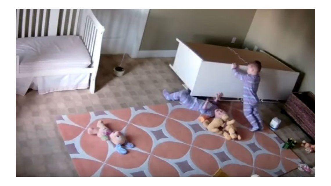 Uno de los gemelos corre el mueble para ayudar a su hermano atrapado
