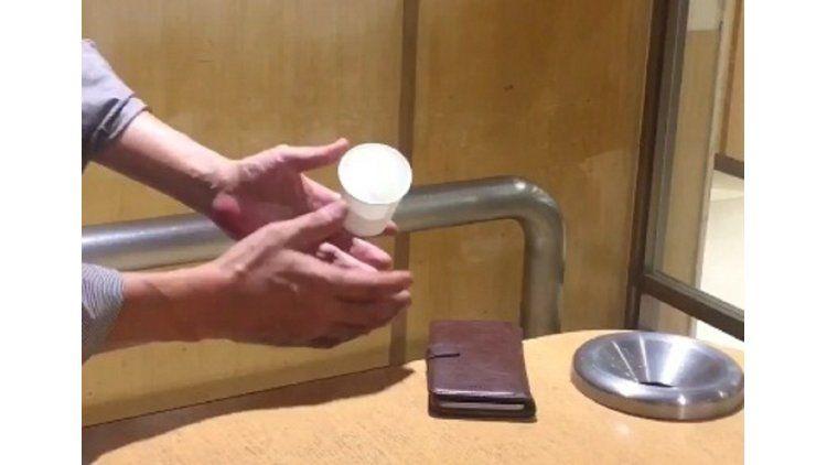 Un truco de magia donde una japonés hace levitar un vaso y un cigarrillo
