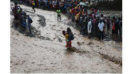 Personas intentan cruzar el río La Digue, en Haití, debido al derrumbe del único puente que conecta con el sur, tras el paso del huracán Matthew.