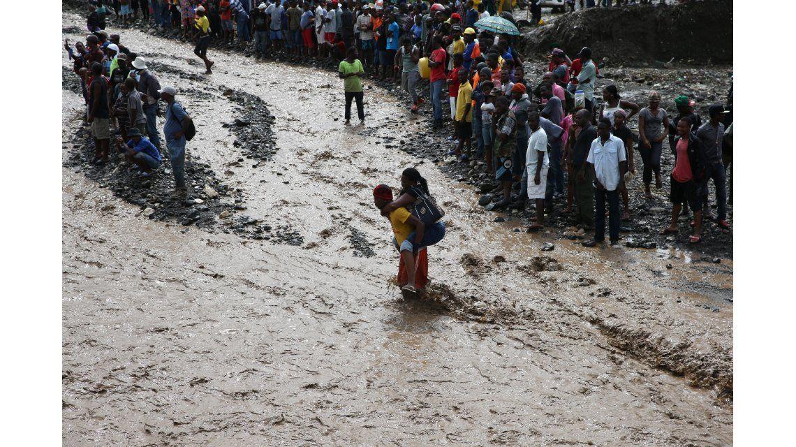 Personas intentan cruzar el río La Digue