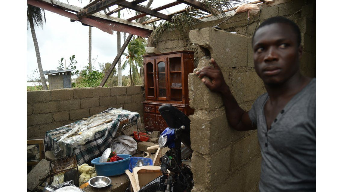 Un joven se para junto a lo que quedó de su hogar en Les Cayes