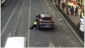 Se llevó a un policía colgado del auto