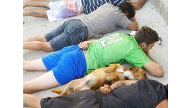 Un perro se tira al piso con su dueño durante un operativo policial