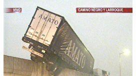 Un camión quedo colgado de un puente en medio de la lluvia