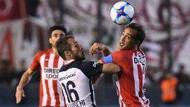 Bellluschi y Desábato pelean por la pelota ante la mirada del Chapu Braña