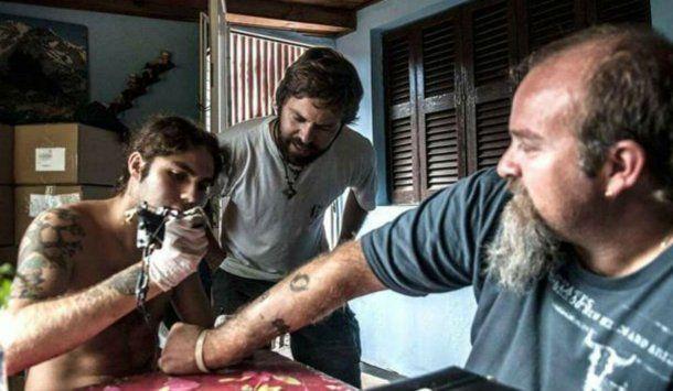 Santiago le hace un tatuaje a Sergio. Con Germán, el otro hermano, de testigo