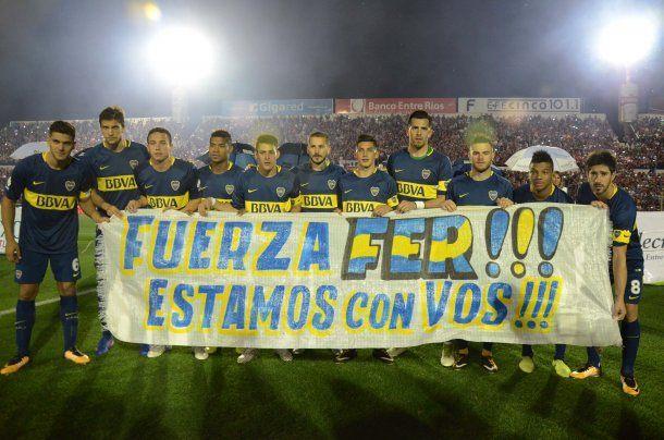 El plantel xeneize con la bandera dedicada a Fernando Gago