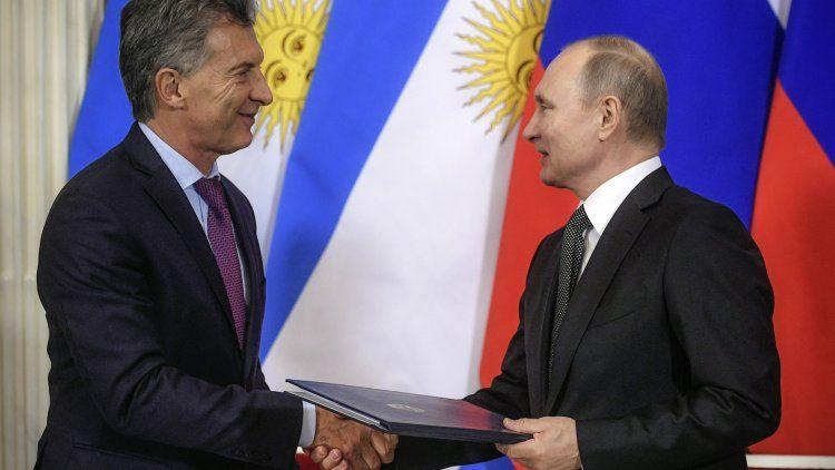 Vladimir Putin y Mauricio Macri intercambian documentos durante una ceremonia.