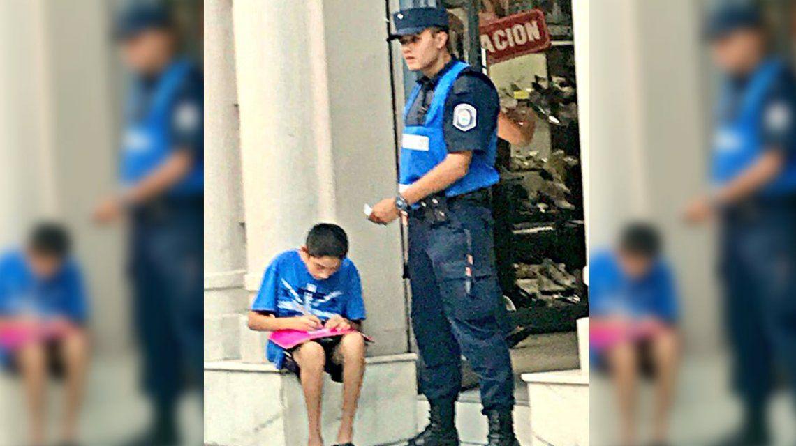 Imagen conmovedora: un policía ayuda a un nene a estudiar en la calle