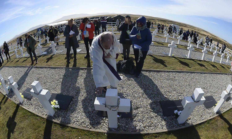 Un sacerdote bendice una de las tumbas
