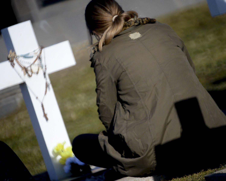 Una de las familiares acompaña la cruz blanca que identifica a su héroe