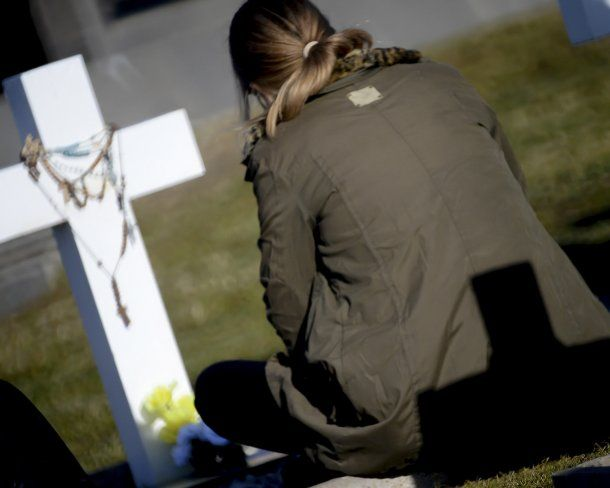 Una de las familiares acompaña la cruz blanca que identifica a su héroe<br>
