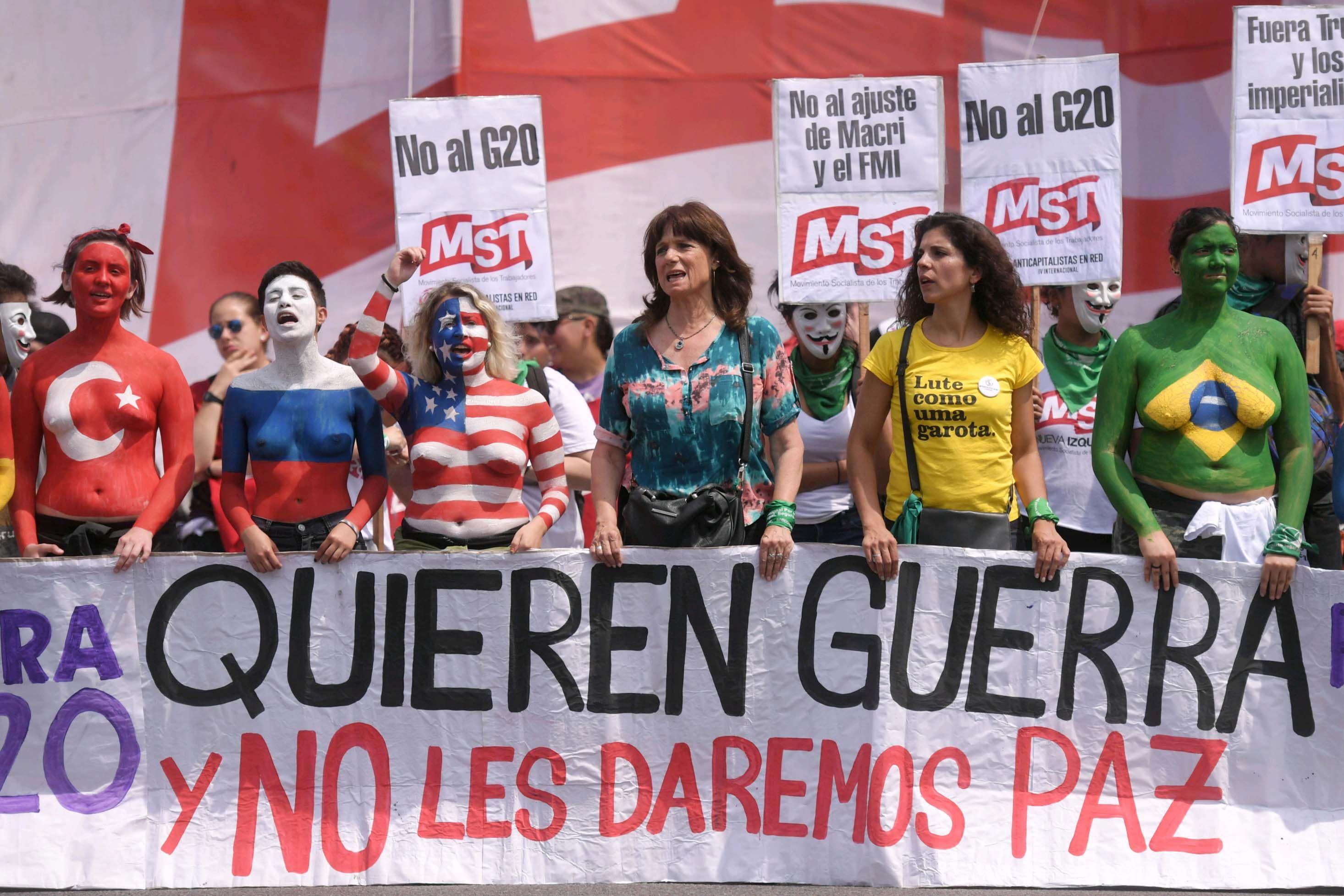 Mujeres con banderas de los países como body painting encabezaron una de las filas