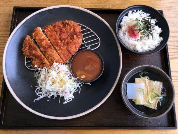Un plato de tonkatsu con verduras, su salsa característica, arroz blanco y sopa de miso<br>