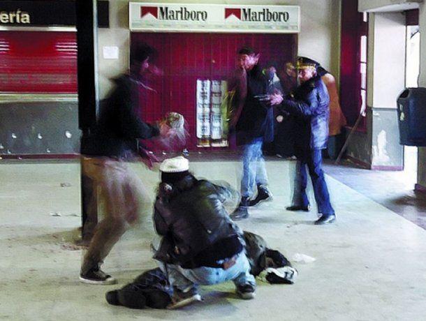 Imagen de Pepe Mateos que muestra a Kosteki asistiendo a Santillán y a Fanchiotti apuntarlo con su fusil. Poco después de esa imagen murió asesinado.