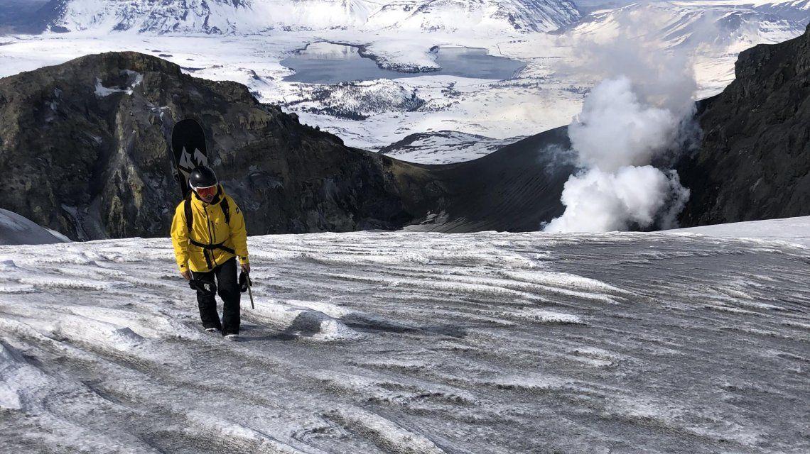 El barilochense Odriozola camina de regreso tras el hito de descender con su tabla por el volcán Copahue