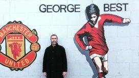 Eric Cantona junto a un mural de George Best