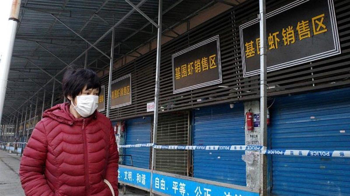 Mercado de Mariscos de Wuhan cerrado con faja y con una persona que circula con barbijo