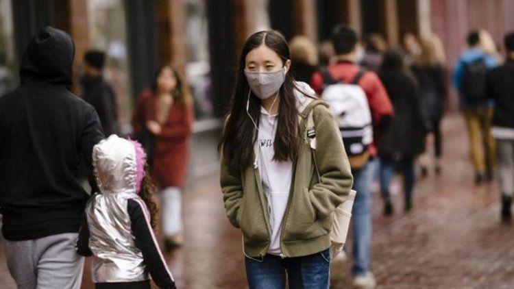 Una mujer camina con barbijo para protegerse del coronavirus Foto: América Económica