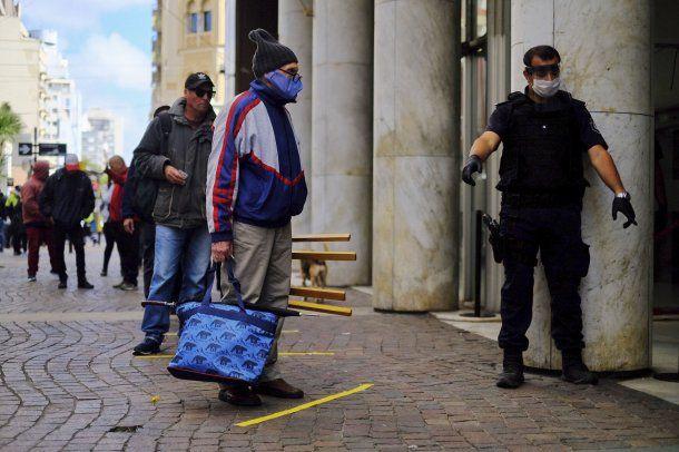 Un jubilado con un banquito se apresta a ingresar a un banco en Mar del Plata