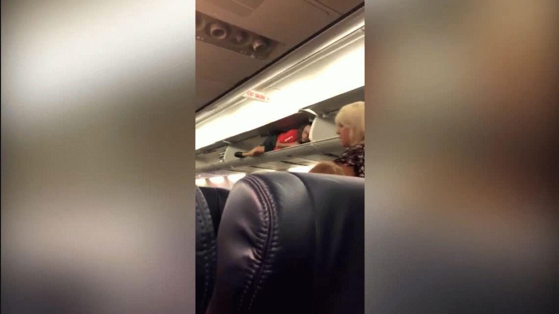 Una azafata se metió adentro del portaequipaje del avión para saludar a los pasajeros