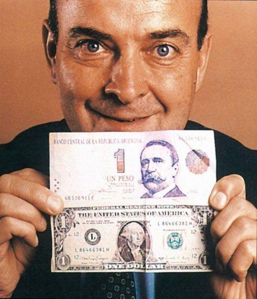 Domingo Cavallo, ministro de Economía y autor intelectual de la Ley de Convertibilidad, posa con un peso argentino y un dólar estadounidense.